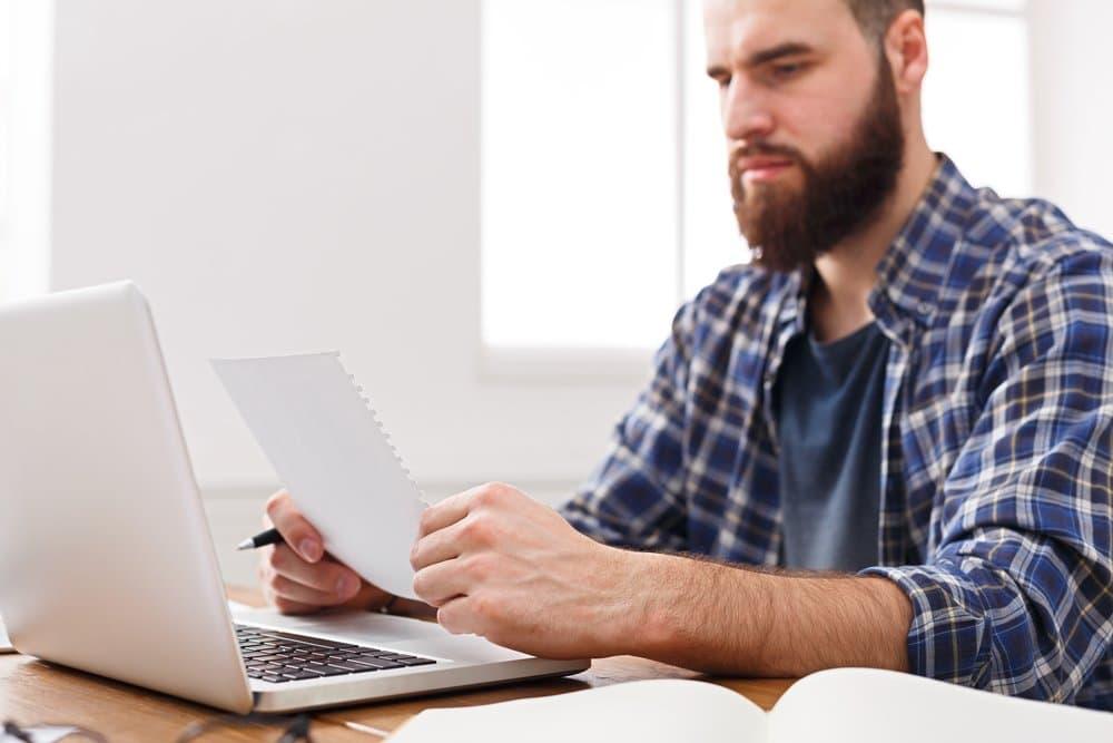 Chico joven en su ordenador y con una factura en la mano