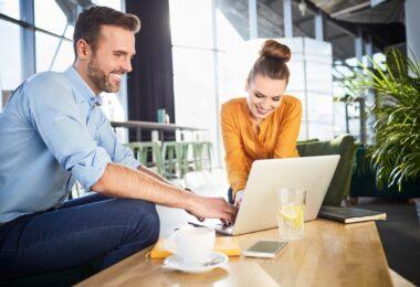 Un chico y una chica miran una factura en el ordenador